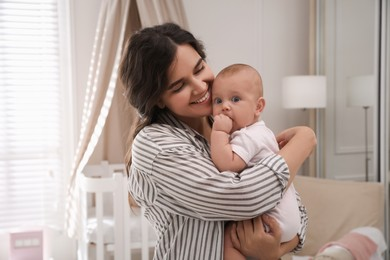 Happy young mother with her cute baby at home