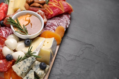 Wooden plate with different delicious snacks on black table, above view. Space for text