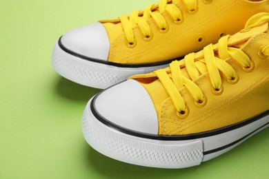 Pair of trendy sneakers on green background, closeup
