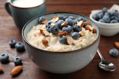 Tasty oatmeal porridge with blueberries and almond nuts on wooden table