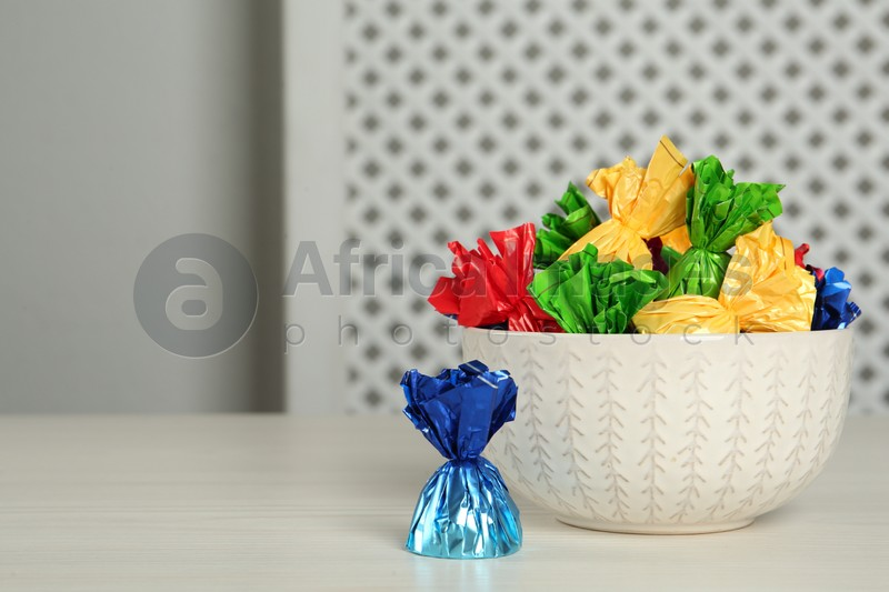 Candies in colorful wrappers on light table, space for text