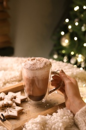 Woman with cup of hot drink and Christmas cookies at home, closeup