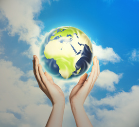 Woman holding Earth against sky, closeup view