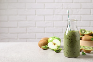 Delicious kiwi smoothie and fresh fruits on light table. Space for text