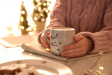 Woman holding cup with hot drink indoors, closeup