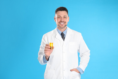 Professional pharmacist with pills on light blue background