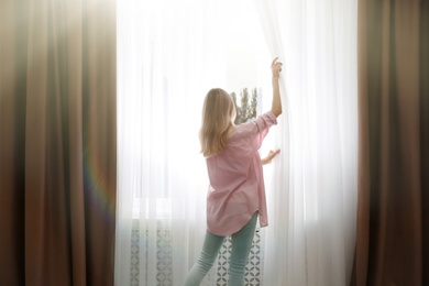 Young woman opening window curtains at home