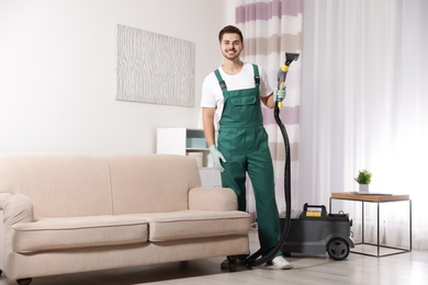 Professional janitor cleaning sofa in living room