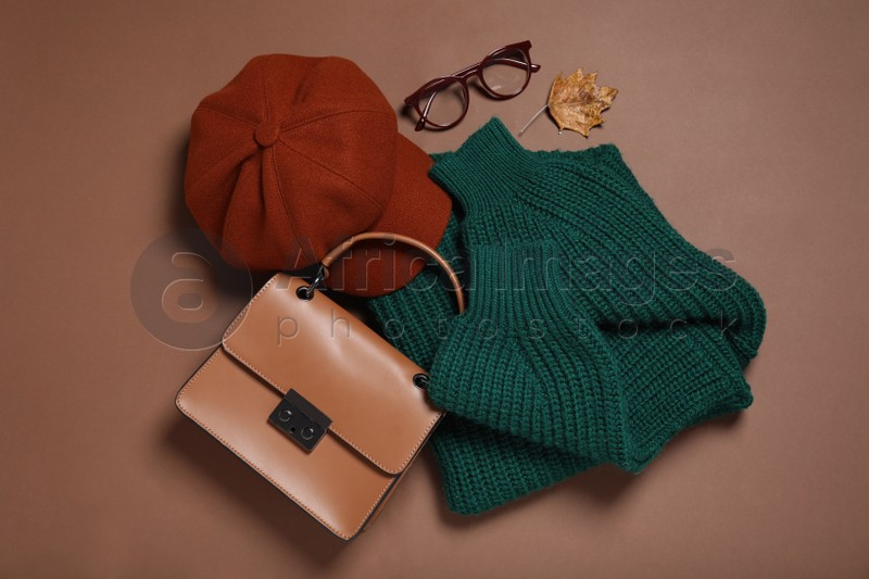 Flat lay composition with stylish hat on brown background