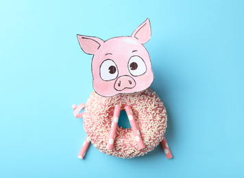 Funny pig made with donut and straws on light blue background, flat lay
