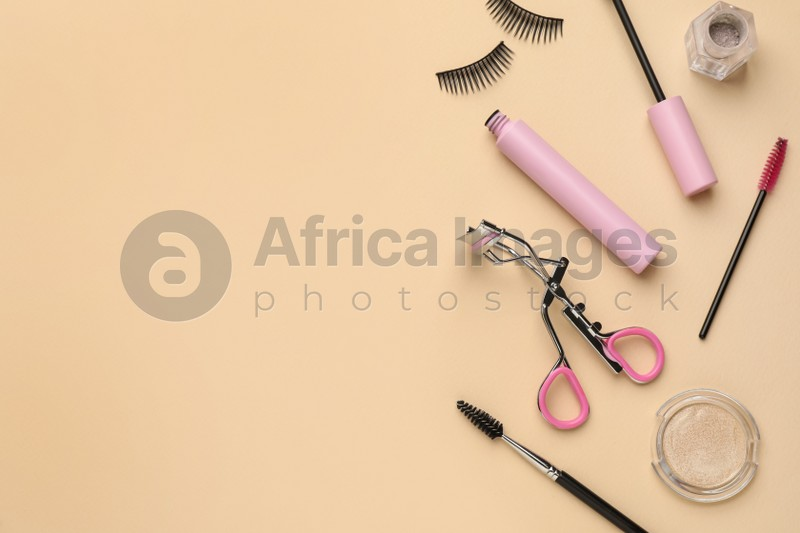 Flat lay composition with eyelash curler, makeup products and accessories on beige background. Space for text