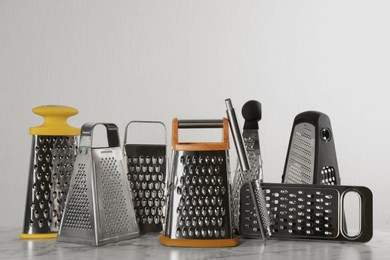 Different modern graters on white marble table