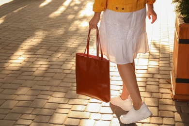 Woman with stylish shopper bag outdoors, closeup. Space for text