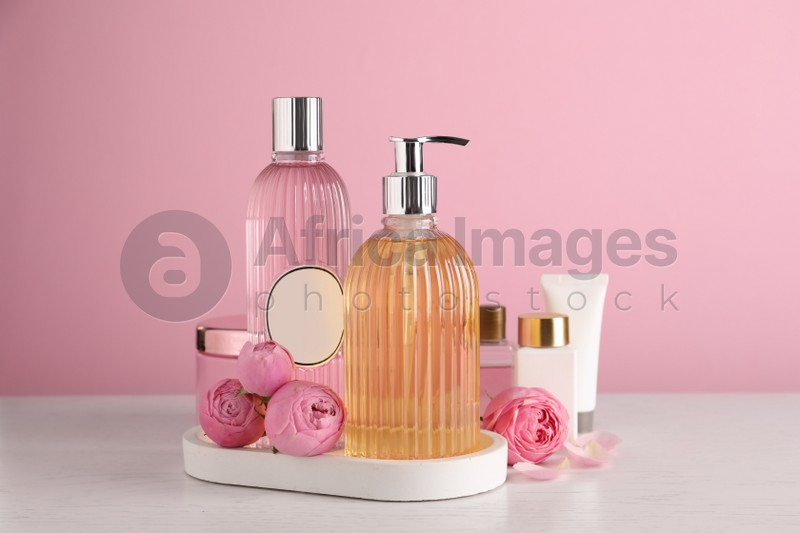 Cosmetic products and flowers on white wooden table
