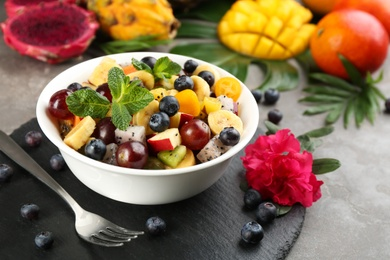 Delicious exotic fruit salad served on grey table