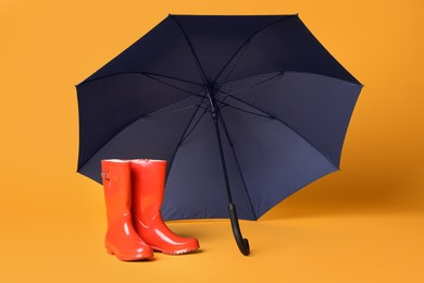 Open blue umbrella and red rubber boots on yellow background