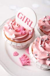Delicious cupcakes with pink cream and Girl topper for baby shower on plate, closeup