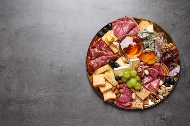 Plate of different appetizers with honey on grey table, top view. Space for text
