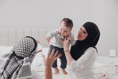 Happy Muslim family with little son in bedroom