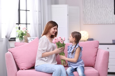 Happy mother and daughter with flowers at home. International Women's Day