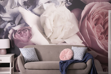 Modern sofa near wall with floral wallpaper. Stylish living room interior
