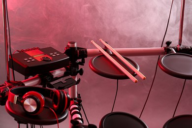 Modern electronic drum kit and smoke on grey background, toned in pink. Musical instrument