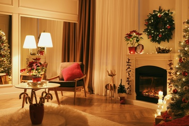 Beautiful living room interior with burning fireplace and Christmas decor in evening