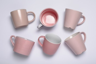 Pink cups on white background, flat lay