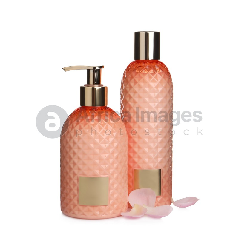 Stylish bottles with cosmetic products and petals on white background