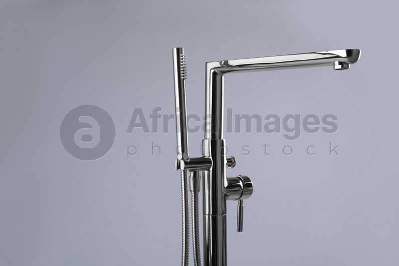 Modern bathtub faucet with hand shower on grey background