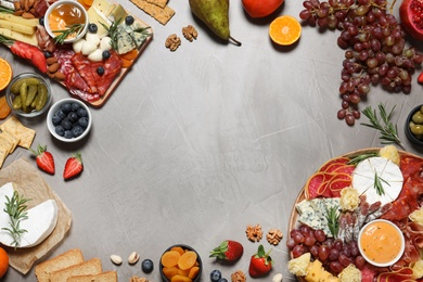 Frame of different delicious snacks on grey table, flat lay. Space for text