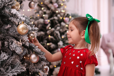 Cute little child near Christmas tree at home