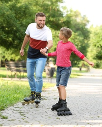 Father and son roller skating in summer park