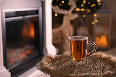 Glass of hot drink near fireplace in room. Space for text