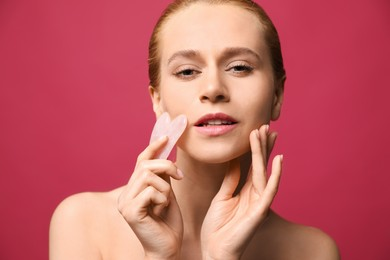 Beautiful young woman doing facial massage with gua sha tool on pink background, closeup