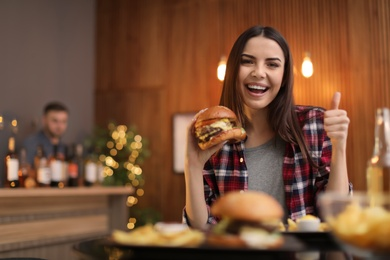 Young woman eating tasty burger in cafe