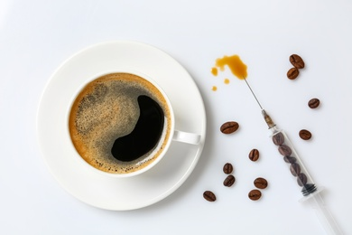 Cup of coffee and syringe with beans on white background, flat lay. Caffeine addiction concept