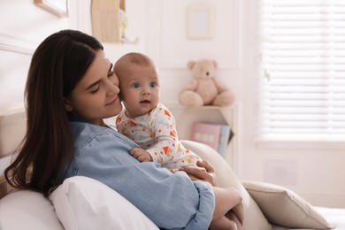 Mother with her cute baby on bed at home