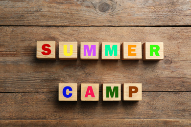 Phrase SUMMER CAMP made with cubes on wooden background, flat lay