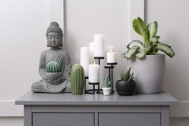Stylish decor with houseplants on grey table near light wall. Interior accessories