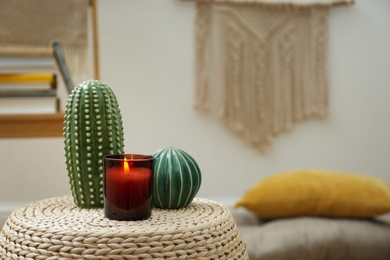 Decorative ceramic cacti and burning candle on wicker stand indoors, space for text. Interior design