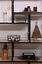 Stylish shelving unit with different decor near white wall indoors. Interior design