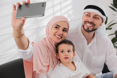 Happy Muslim family taking selfie on sofa at home