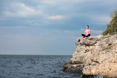 Young woman meditating on cliff near river. Space for text
