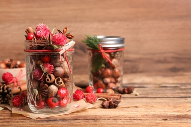 Aromatic potpourri in glass jar on wooden table. Space for text