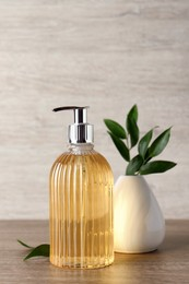 Stylish dispenser with liquid soap and green leaves in vase on wooden table