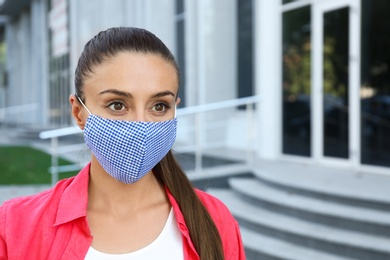 Woman wearing handmade cloth mask outdoors, space for text. Personal protective equipment during COVID-19 pandemic