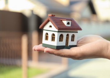 Real estate agent holding house model outdoors, closeup