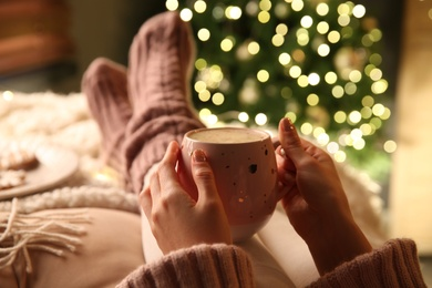 Woman holding cup of delicious hot drink near Christmas tree indoors, closeup