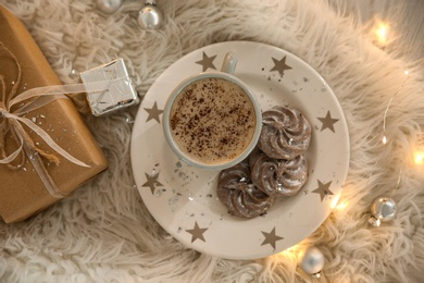 Tasty hot drink, cookies, gift and Christmas lights on fur, flat lay